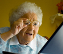Senior woman having trouble reading the computer screen